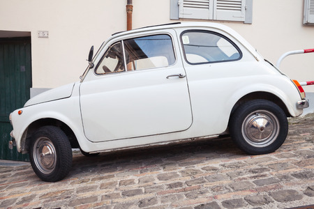 used car: Fermo, Italy - February 11, 2016: Old white fiat 500 L city car on the street of Italian town, side view