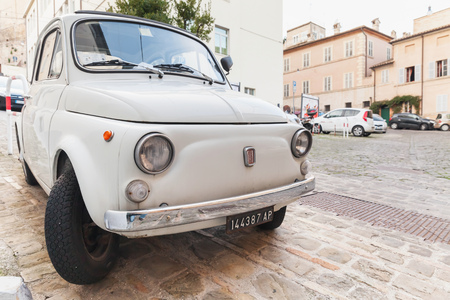 old towns: Fermo, Italy - February 11, 2016: Old white fiat 500 L city car on the street of Italian town, closeup front view Editorial