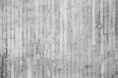 Gray concrete wall with relief pattern from timber formwork, background photo texture