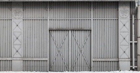 ridged: Old storage building wall made of ridged steel panels with gate Stock Photo