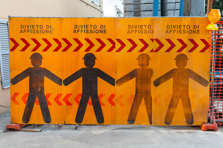 posting: Construction site border with warning signs and text on Italian means post no bills posting Stock Photo