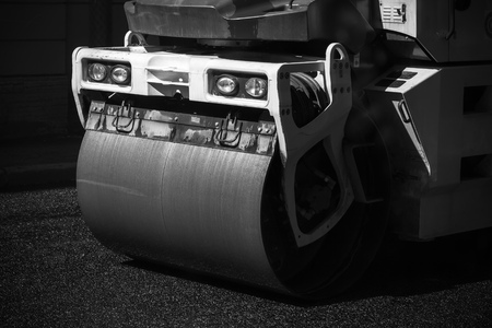 asphalting: Fragment of roller, urban road is under construction, asphalting in progress. Black and white photo Stock Photo