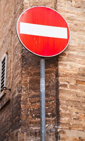 metal pole: Round red sign No Entry on metal pole near old brick wall