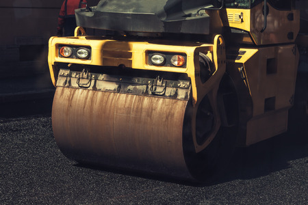 asphalting: Fragment of yellow roller, urban road is under construction, asphalting in progress, vintage tonal correction photo filter effect