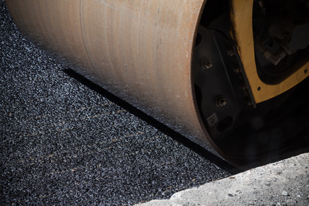 asphalting: Fragment of roller wheel, urban road is under construction, asphalting in progress Stock Photo