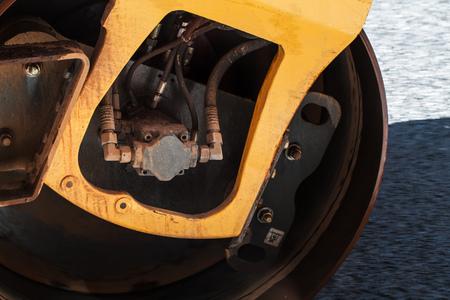 asphalting: Fragment of yellow roller wheel, urban road is under construction, asphalting in progress