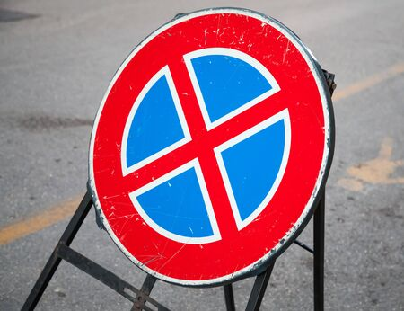 under: Round road sign stands on urban roadside, standing is prohibited