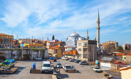 fatih: Izmir, Turkey - February 7, 2015:  Street view with Fatih Camii Esrefpasa old mosque. Sellers of vegetables prepare products for sale Editorial