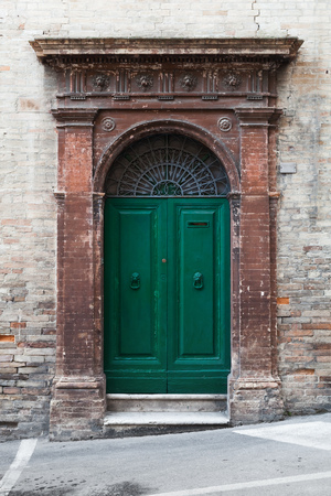 italian architecture: Old Italian architecture details. Green wooden door with arch and decoration in old brick wall, background photo texture
