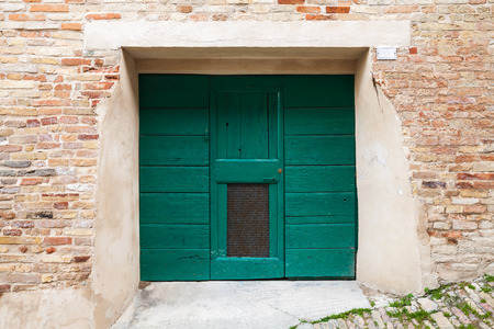 italian architecture: Old Italian architecture details. Green wooden gate in old brick wall, background photo texture