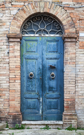 italian architecture: Old Italian architecture details. Blue wooden door with arch in old brick wall, background photo texture Stock Photo