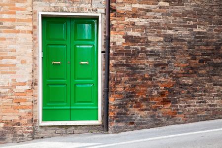 italian architecture: Old Italian architecture details. Green wooden door in old brick wall, background photo texture Stock Photo