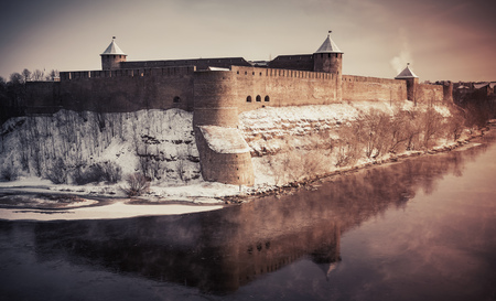 tonal: Ivangorod fortress at Narva river in winter season. Border between Russia and Estonia. Vintage stylized photo with tonal correction photo filter and vignette effect Editorial