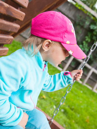 baseball swing: Outdoor portrait of funny little child in a pink baseball cap on a swing