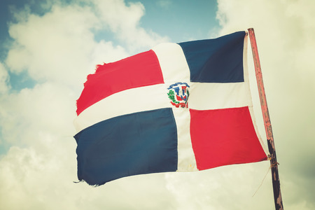 tonal: Flag of Dominican republic is waving on wind over blue cloudy sky background, old style photo filter effect with warm tonal correction Stock Photo