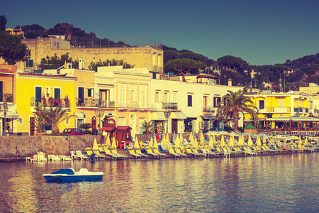 tonal: Main coastal street of Lacco Ameno. Ischia island, Mediterranean Sea coast, Bay of Naples, Italy. Vintage stylized photo with warm tonal correction retro filter effect Stock Photo