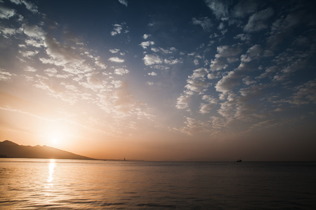 tonal: Dramatic colorful seascape. Sun, evening sky and sea background photo with high contrast tonal correction photo filter effect