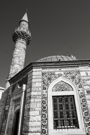 camii: Ancient Camii mosque, facade fragment with minaret. Konak square, Izmir, Turkey. Monochrome photo