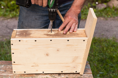 chippy: Wooden birdhouse is under construction, carpenter works with drill, close-up photo Stock Photo