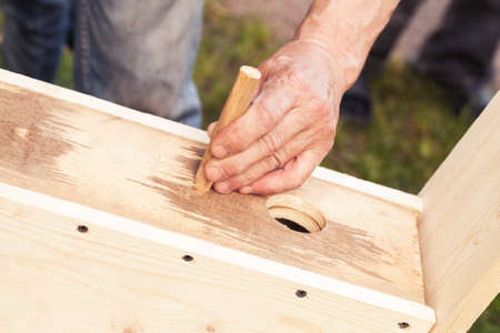 adds: Birdhouse made of wood is under construction, carpenter adds detail