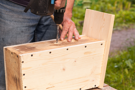 chippy: Wooden birdhouse is under construction, carpenter works with drill, closeup photo Stock Photo