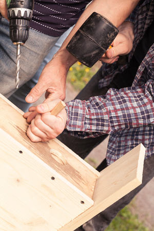 chippy: Wooden birdhouse is under construction, carpenters work with rubber hummer and drill