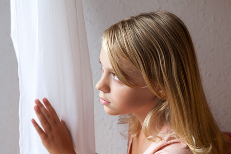 window curtains: Beautiful blond Caucasian girl looking in a window with white curtains, closeup portrait