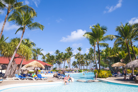cana: Punta Cana, Dominican republic - January 10, 2015: Ordinary tourists relaxing in Punta Cana Bavaro Princess resort hotel with pool under palms near the beach