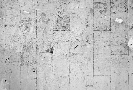 damaged: Damaged old gray wall with artificial stone tiling, background photo texture
