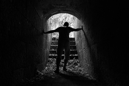 way out: Young tired man leaves dark stone tunnel with glowing end, black and white photo Stock Photo