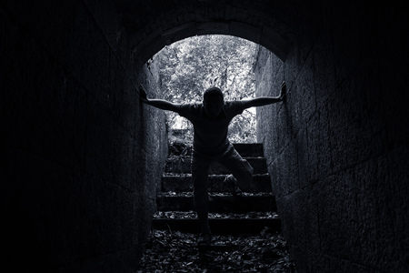 catacomb: Young man enters dark stone tunnel black and white lo key photo Stock Photo