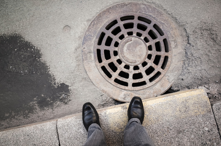 urbanite: Urbanite man in black new shining leather shoes standing on the roadside near rusty sewer manhole