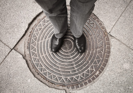 urbanite: Urbanite man in black new shining leather shoes standing on rusty sewer manhole Stock Photo