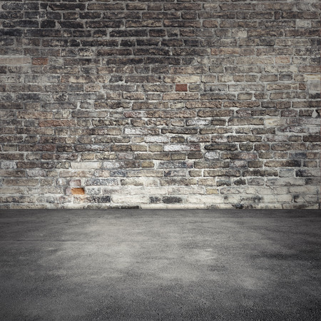 Empty abstract interior background with dark old brick wall and asphalt floor