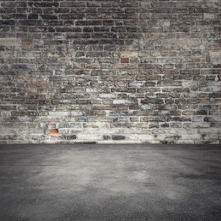 Vide abstrait intérieur avec vieux mur de brique sombre et le plancher d'asphalte