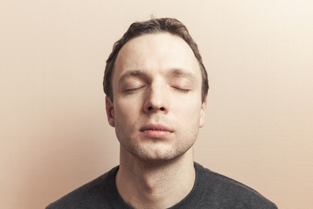 tonal: Young Caucasian man with closed eyes. Studio portrait over gray wall background, old style photo filter tonal correction effect