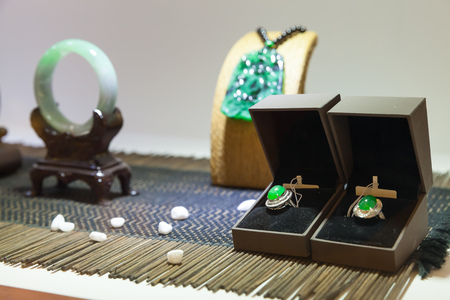 nephritis: Hangzhou, China - December 2, 2014: Traditional Chinese stone amulets and earrings made of jade stands in wooden holder on a counter in gemstones shop
