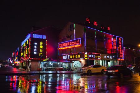 Hangzhou, Cina - 3 dicembre 2014: via cinese della città di notte con le luci al neon variopinte della pubblicità sulle pareti