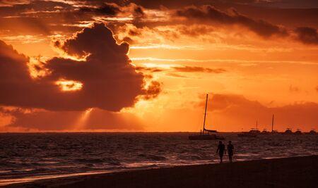 red morning: Coastal Caribbean seascape at sunrise. Atlantic ocean coast, sandy beach in red morning sunlight