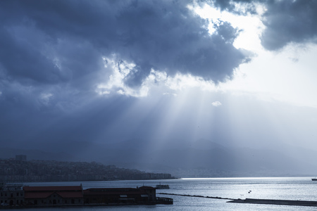Dark dramatic seascape with clouds and sunlight rays over sea. Blue toned photo filter effect
