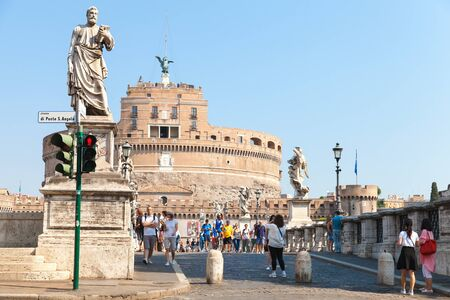 pert: Rome, Italy - August 8, 2015: Tourists walk near statues on Saint Angelo Bridge. Old central pert of Rome in summer
