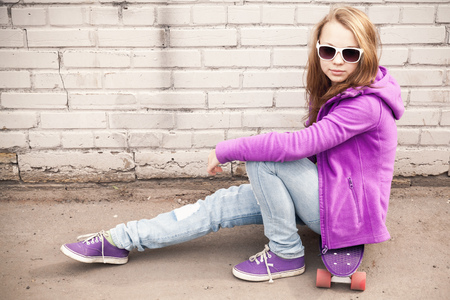 tonal: Blond teenage girl in jeans and sunglasses sits on skateboard near white brick wall, photo with warm retro tonal correction effect, old style filter Stock Photo