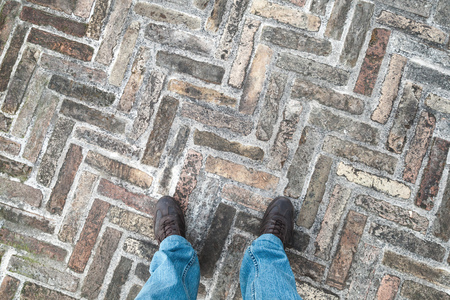 urbanite: Feet of an urbanite man in jeans standing on old cobblestone pavement Stock Photo