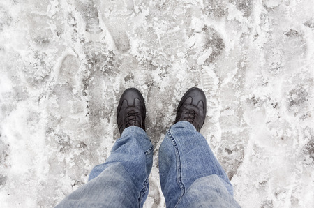 dirty feet: Male feet in blue jeans standing on wet dirty snow
