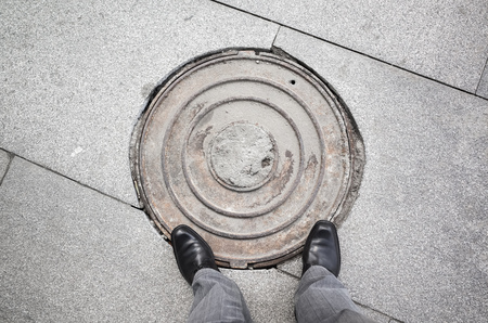 urbanite: Feet of an urbanite man in black new shining shoes standing on rusty sewer manhole