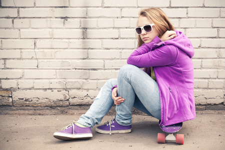 tonal: Blond teenage girl in jeans and sunglasses sits on her skateboard near white brick wall, photo with warm retro tonal correction effect, old style filter Stock Photo