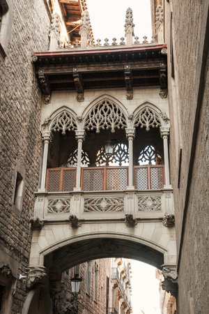 carrer: Ancient arch and balcony over Carrer del Bisbe, Gothic Quarter, Barcelona. Vertical photo