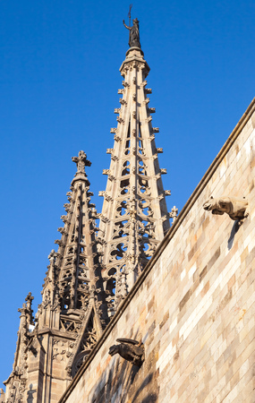 spires: Cathedral of the Holy Cross and Saint Eulalia also known as Barcelona Cathedral. Roof fragment with spires over blue sky