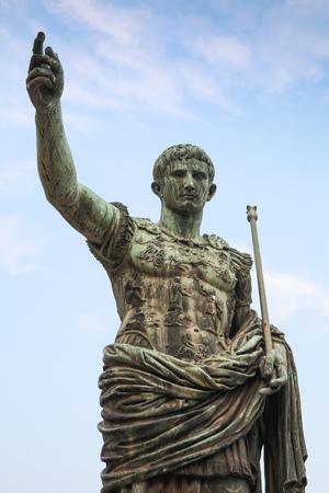 spqr: Antigua estatua SPQR IMP C�sar Augusto PATRIAE PATER sobre el cielo nublado. Calle Via dei Fori Imperiali, Roma, Italia