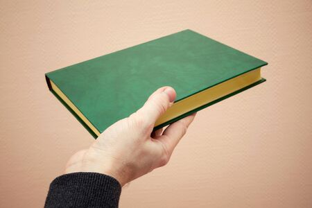 tonal: Book with empty dark green leather cover in male hand, old style warm tonal correction photo filter effect